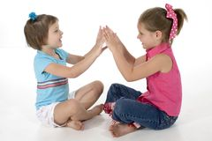 Clapping Games. Two sisters, 4 and 6, playing clapping games stock image