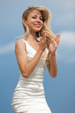 Clapping girl. Attractive young woman in white dress clapping her hands and smiling on the background of the blue sky Stock Photos