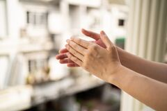 Clapping hands at balcony to show gratitude to health care worker