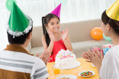 Clapping hands. Image of a cheerful b0day girl clapping hands with her parents on the foreground stock image