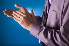 Clapping man's hands. Blue background in the studio Stock Photos