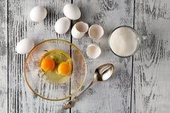 Clara de huevo y yemas de huevo separadas en dos cuencos y shel quebrado del huevo Fotos de archivo