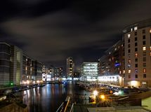 Clarence dock leeds at night with moored barges and moonlit clouds over brightly illuminated waterside buildings reflected in the. Harbour royalty free stock photo