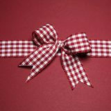 Claret greeting card with red white checked ribbon Stock Photo