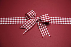 Claret greeting card with red white checked ribbon Royalty Free Stock Photo
