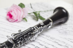 Clarinet with red rose. On sheet music royalty free stock images