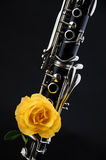 Clarinet With Yellow rose. A soprano clarinet with a yellow rose against a black background in the vertical format with copy space royalty free stock photography