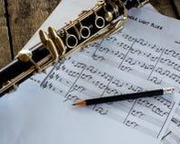 Clarinetto e strato di musica su fondo di legno Fotografie Stock