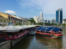 Clarke Quay marine style eatery with dining on docked boat and sailor design on Singapore River Royalty Free Stock Images