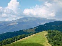 Claro en cresta de montaña con el bosque en cuestas en Cárpatos imagenes de archivo