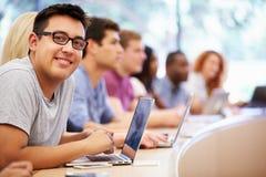 Clase de estudiantes universitarios que usan los ordenadores portátiles en conferencia foto de archivo libre de regalías