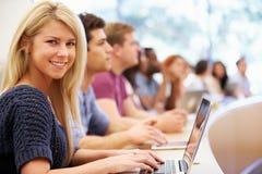 Clase de estudiantes universitarios que usan los ordenadores portátiles en conferencia foto de archivo