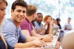 Clase de estudiantes universitarios que usan los ordenadores portátiles en conferencia fotografía de archivo libre de regalías