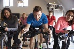 Clase de giro en las bicicletas estáticas en un gimnasio que mira a la cámara imagen de archivo