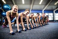 Clase de la aptitud en la posición del tablón con pesas de gimnasia Fotografía de archivo