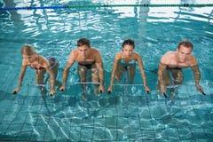 Clase de la aptitud que hace aeróbicos de la aguamarina en las bicicletas estáticas fotos de archivo