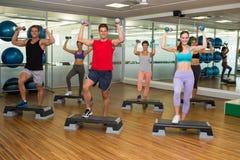 Clase de la aptitud que hace aeróbicos del paso con pesas de gimnasia Imagen de archivo