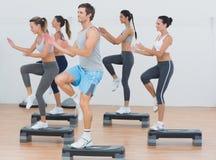 Clase de la aptitud que realiza ejercicio de los aeróbicos del paso Imagen de archivo