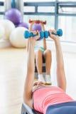 Clase de la aptitud que realiza ejercicio de los aeróbicos del paso con pesas de gimnasia Imagen de archivo libre de regalías