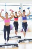 Clase de la aptitud que realiza ejercicio de los aeróbicos del paso con pesas de gimnasia Imagenes de archivo