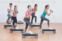 Clase de la aptitud que realiza ejercicio de los aeróbicos del paso con pesas de gimnasia Imagen de archivo