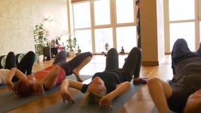 Clase de la yoga de gente que ejercita forma de vida sana en yoga del estudio de la aptitud almacen de video