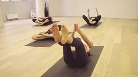 Clase de la yoga Gente que hace ejercicios de la yoga