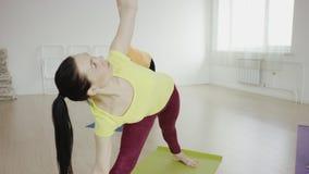 Clase de la yoga que hace actitud de la cobra junto en las esteras del ejercicio en el gimnasio almacen de video