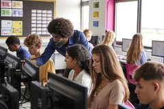 Clase de Working In Computer del estudiante de la escuela secundaria de Helping Teenage Female del profesor de sexo masculino fotografía de archivo libre de regalías