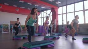 Clase del ejercicio de los aeróbicos del paso - grupo de personas que ejercita en steppers con el instructor almacen de metraje de vídeo