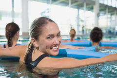 Clase feliz de la aptitud que hace aeróbicos de la aguamarina con los rodillos de la espuma Foto de archivo