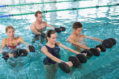 Clase feliz de la aptitud que hace aeróbicos de la aguamarina con pesas de gimnasia de la espuma Foto de archivo