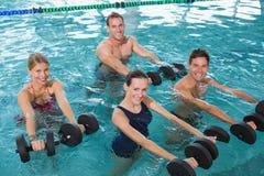 Clase feliz de la aptitud que hace aeróbicos de la aguamarina con pesas de gimnasia de la espuma Fotografía de archivo