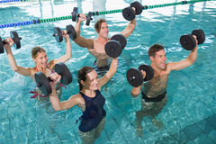 Clase feliz de la aptitud que hace aeróbicos de la aguamarina con pesas de gimnasia de la espuma Imagenes de archivo