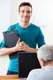 Clase feliz del ordenador de Holding Clipboard In del profesor de sexo masculino imagen de archivo