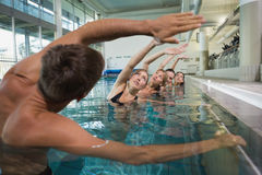 Clase femenina de la aptitud que hace aeróbicos de la aguamarina con el instructor de sexo masculino Fotografía de archivo libre de regalías