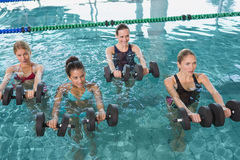 Clase femenina de la aptitud que hace aeróbicos de la aguamarina con pesas de gimnasia de la espuma Fotos de archivo libres de regalías