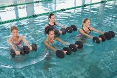 Clase femenina de la aptitud que hace aeróbicos de la aguamarina con pesas de gimnasia de la espuma Imágenes de archivo libres de regalías