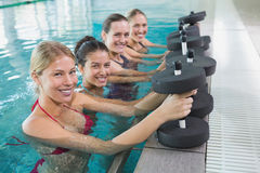 Clase femenina de la aptitud que hace aeróbicos de la aguamarina con pesas de gimnasia de la espuma Fotografía de archivo