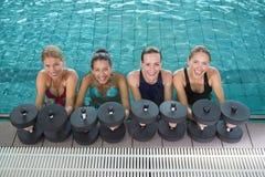Clase femenina de la aptitud que hace aeróbicos de la aguamarina con pesas de gimnasia de la espuma Fotografía de archivo libre de regalías