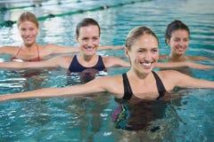 Clase femenina sonriente de la aptitud que hace aeróbicos de la aguamarina Imagenes de archivo