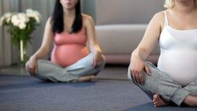 Clase prenatal de la yoga para que mujeres embarazadas permanezcan en forma y entonen sus músculos fotos de archivo