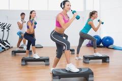 Clase que realiza ejercicio de los aeróbicos del paso con pesas de gimnasia Foto de archivo libre de regalías