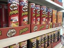 Clases de productos de Pringles en estantes de un supermercado foto de archivo libre de regalías