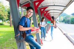 Clases particulares de los estudiantes de la universidad y libro de lectura asiáticos jovenes en el walkwa Imágenes de archivo libres de regalías