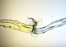 Clash of yellow and blue liquid jets Stock Photos