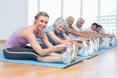 Clasifique estirar las manos a las piernas en la clase de la yoga Fotos de archivo libres de regalías