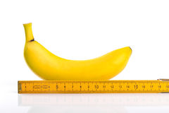 Clasifique las materias concepto, plátano con la regla aislada en blanco imagen de archivo