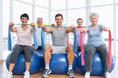 Clasifique sostener las correas del ejercicio mientras que se sienta en bolas de la aptitud fotos de archivo