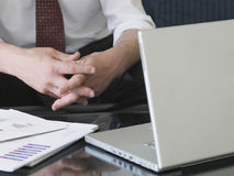 Clasped Business Hands By Laptop Stock Photo